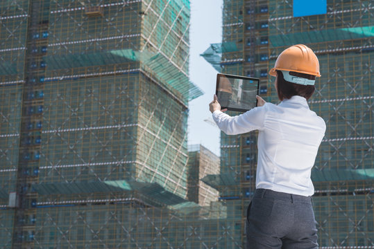 Female investor taking photo of building at the construction site
