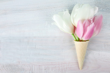 tulips pink and white in a waffle cone on a wooden background