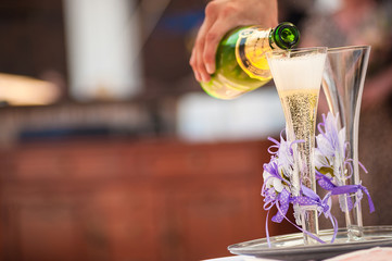 Waiter pours a glass of champagne at the wedding