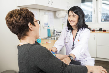 Doctor Adjusting Band On Patient's Hand