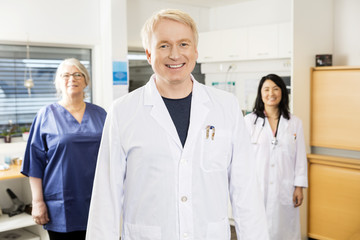 Medical Professional Smiling While Standing With Team In Clinic