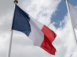 France flag on the mast under cloudy blue sky