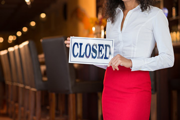 Cropped image of waitress showing closed sign