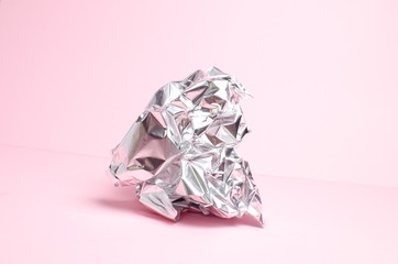 wrinkled and aluminum foil on a pink background