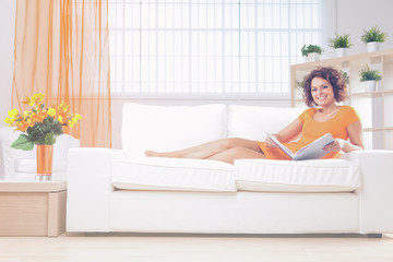 beautiful smiling young woman with orange dress read on a couch indoor