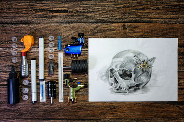Tattoo still life with skull sketch and tattoo tools on wooden background