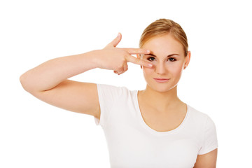 Young woman with victory sign on eye
