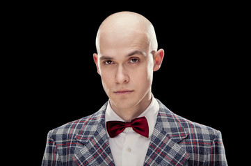 Young alluring bald caucasian man professor or teacher with red bow tie black isolated