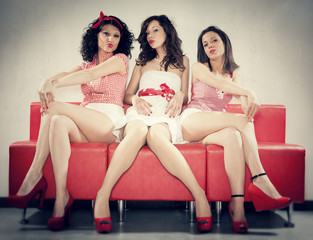 three pin-up girl sit on a red sofa