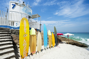 Colorful surfboards stand lined up on the beach at Arpoador in Rio de Janeiro, Brazil