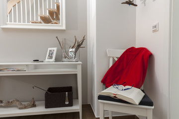 Stuhl mit Buch und Lesebrille im Flur