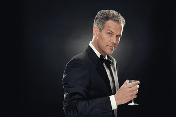 handsome businessman drink martini isolated on black