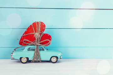 Background with miniature blue toy car carrying a heart on blue