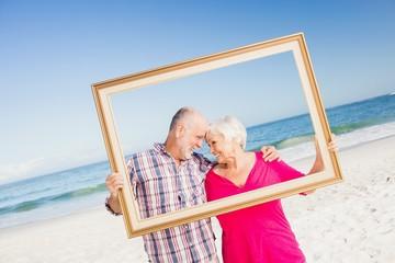 Senior couple holding frame
