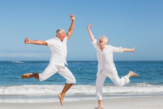 Senior couple jumping at the beach