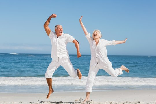 Senior couple jumping at the beach