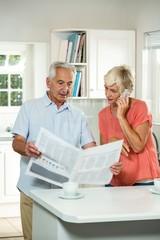 Senior man reading newspaper while woman talking on phone