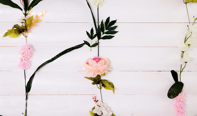 Artificial flowers on wood background