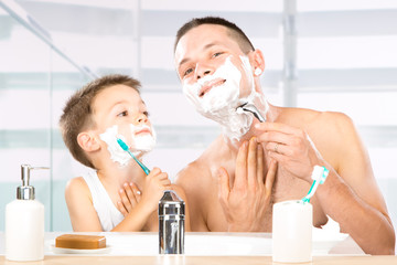 happy child have fun with dad with shaving foam in the bathroom