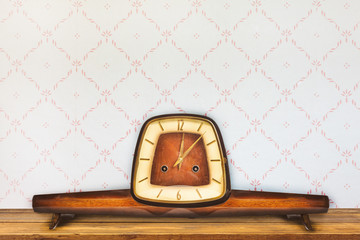 Vintage table clock in front of retro wallpaper