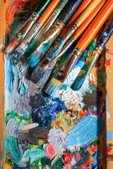 Colourful oil paint, different types of brushes and palette