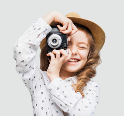 Cute little girl takes picture with vintage camera