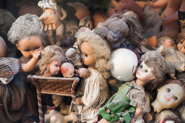 Scary broken doll heads heap in a shop