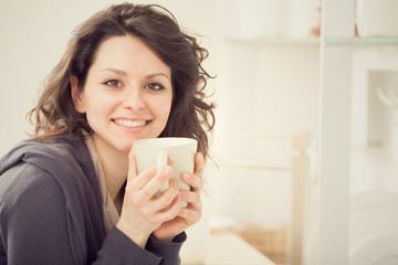 young smiling girl with cup of tea in the kitchen