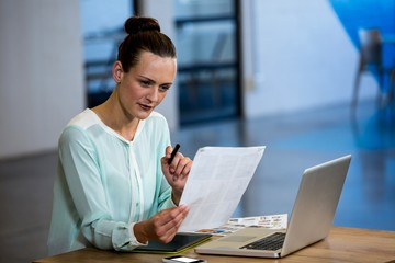 Woman looking a chart with laptop and graphics tablet on desk