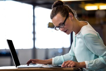 Woman looking a chart and using a laptop in office