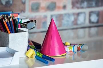 Party horn, birthday hat, pen holder and spectacle on desk