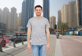 young man in gray t-shirt and jeans over city