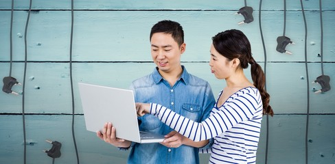 Composite image of couple using laptop
