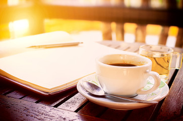 workplace, coffee cup on wooden table - over sunlight [blur and select focus background]