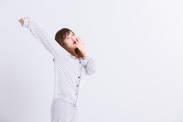 アクビをするパジャマの女性