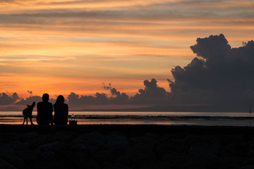couple watching sunrise with dog