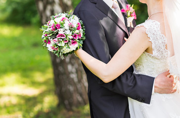 bride and groom with bouquet of flowers outdoor
