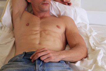 Muscular, handsome, shirtless man relaxing on  bed