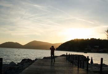 a man silhouette taking pictures at the sunset landscape