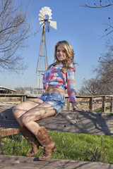 Cowgirl sitting on fence with windmill in background