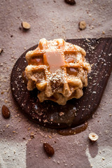 Belgian sugar waffles with grated nuts and caramel syrup