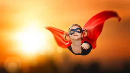 child girl superhero flying through sky at sunset