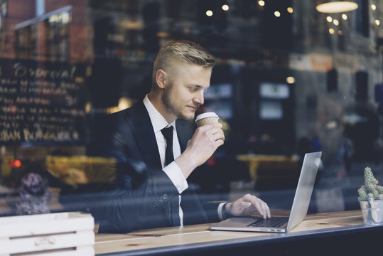 Close-up of young successful businessman wearing black suit and using modern laptop in coffee shop while reading in internet information
