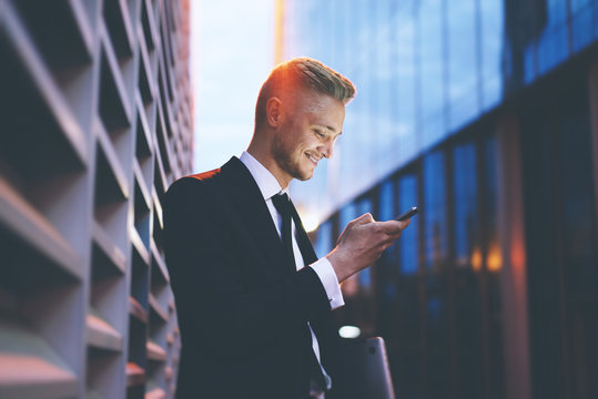 Happy smiling businessman wearing black suit and using modern smartphone near his office at early morning, successful employer to make a deal while standing near skyscraper