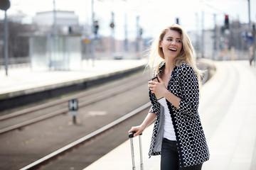 Frau mit Handy am Bahnhof