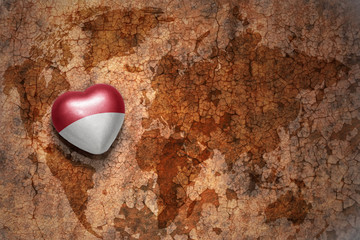 heart with national flag of monaco on a vintage world map crack paper background. concept