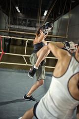 female kick boxer practicing attack.