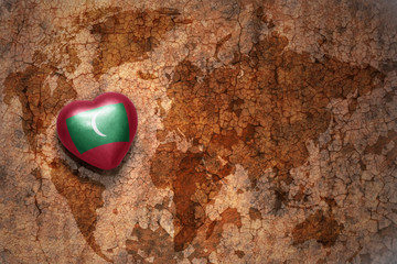 heart with national flag of maldives on a vintage world map crack paper background.