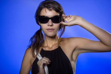 Female teen wearing sunglasses on vivid background lit with blue color gels