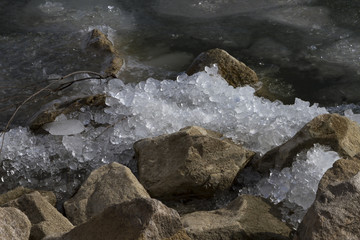 Ice crushed on the rocks along the shoreline of a partially frozen lake.